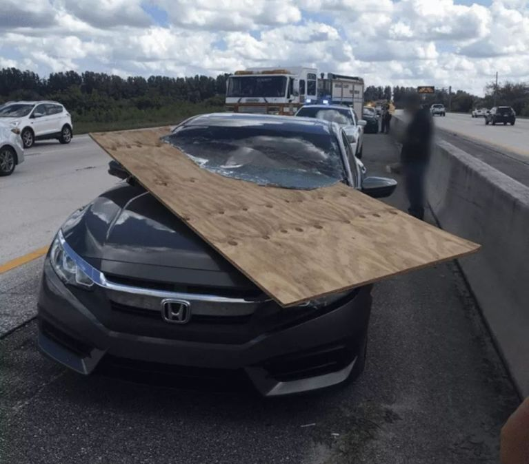 A lucky driver was mostly unscathed after a large piece of plywood impaled the vehicle's windshield.