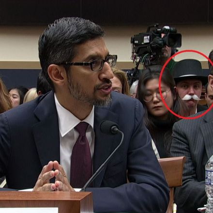 A person dressed up like the Monopoly man is sat behind Google's CEO as he testified in Congress