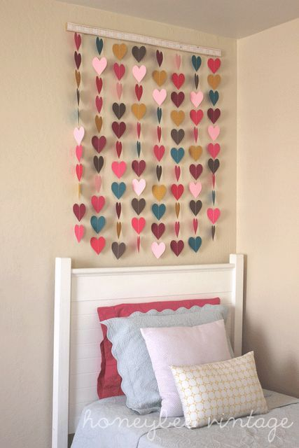 If you want to make a cute decoration either for your bedroom or maybe for the nursery, you can use colored paper to cut out heart shapes and then you can sew them to make strands and to hang them above the bed or anywhere else on the wall or under a shelf.