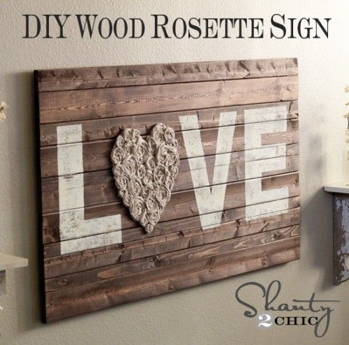"If you don't particularly like paintings, you can try something different. Maybe a wood sign would be a better idea. This one has the work ""love"" written on it and the ""o"" is actually a heart made of fabric flowers that were glued to the sign. It's chic and has a certain vintage flair to it."